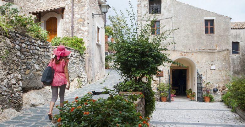 Ragazza a piedi attraverso le tipiche stradine di Castelmola, un piccolo villaggio turistico vicino a Taormina, Sicilia