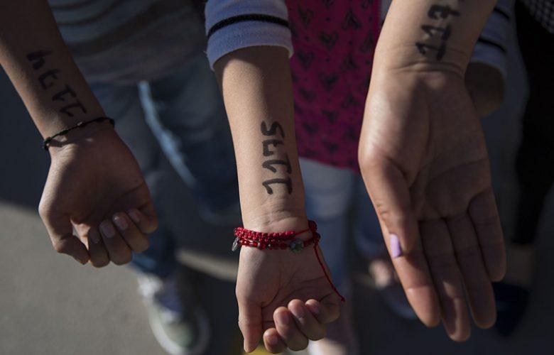 Bambini migranti in attesa al confine tra Messico e Stati Uniti con i numeri marchiati sul braccio